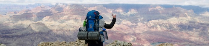 Student wearing a backpack, overlooking Grand Canyon, with their horns up.